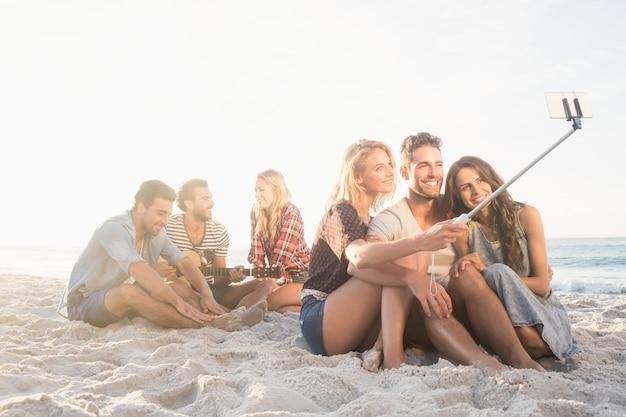 砂の歌の上に座ってselfiesを撮って友達に笑顔