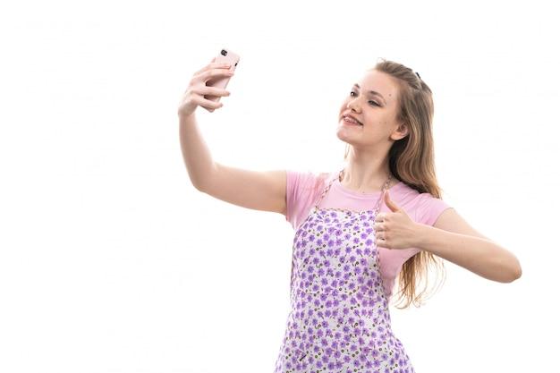 正面の若い美しい主婦ピンクのシャツでカラフルなケープ幸せな笑顔selfiesを取って
