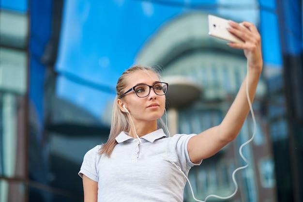 事務所ビルの前でselfiesを作るメガネのビジネスウーマン。海外のビジネスパートナーの写真を撮る笑顔の女性。