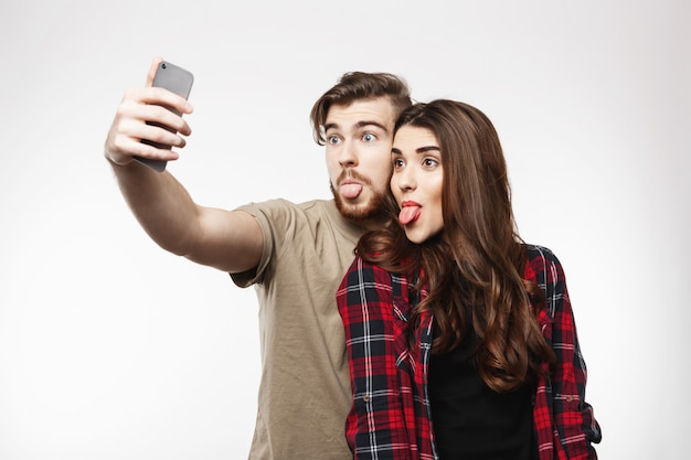 陽気なカップルが楽しんでいる電話を作る顔でselfiesを取る