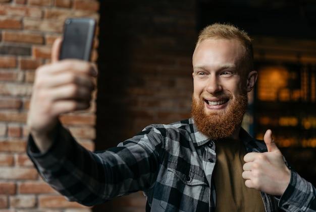 Selfiesを取って、携帯電話を使用してひげを生やした男