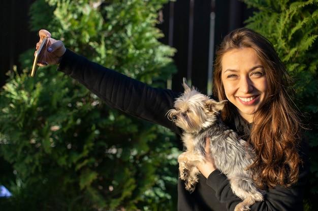 かわいい女の子は感情的にヨークシャー犬とselfiesを作る