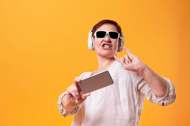 流行に敏感な女性selfiesを取り、音楽を聴く