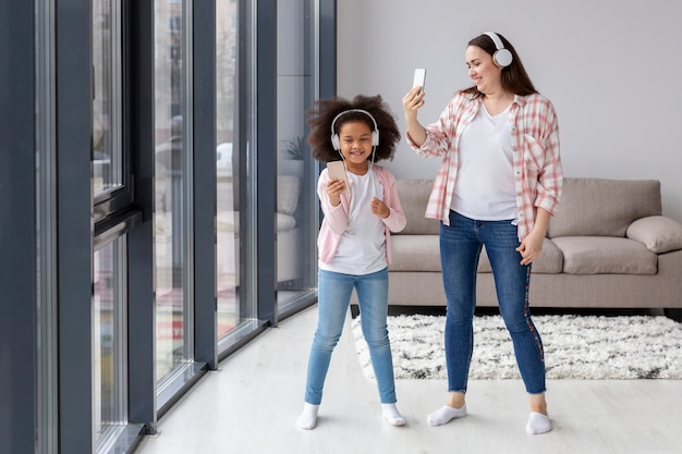 正面母と娘が自宅でselfiesを取る