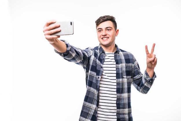 彼の携帯電話で面白いselfiesを取って陽気なティーンエイジャー