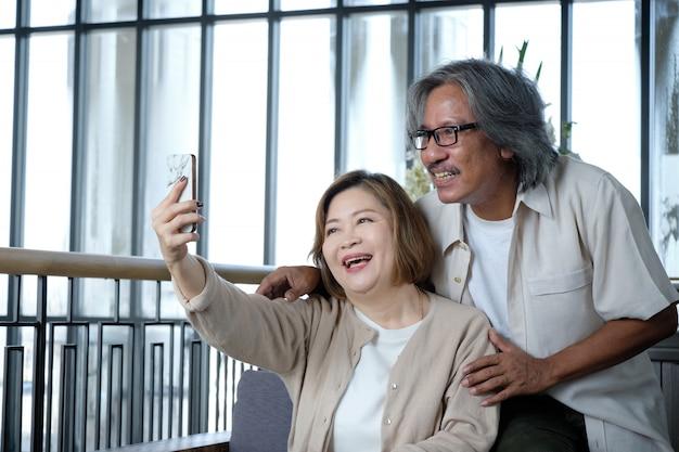 年配のカップルがselfiesの写真を撮って、幸せそうに見えて、休暇中に暖かい。
