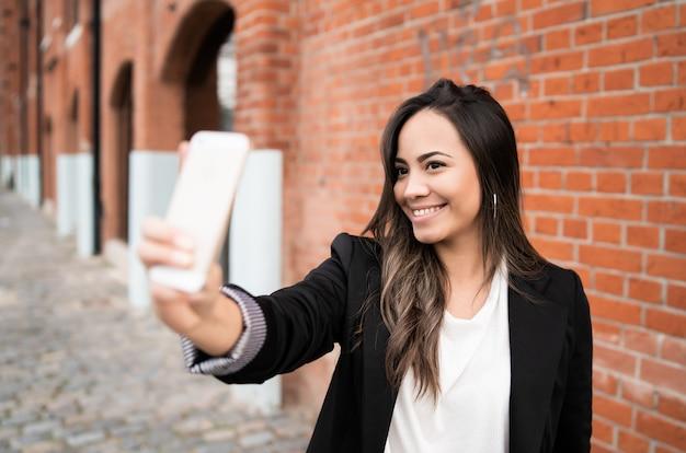 Молодая женщина, принимая selfies с телефоном.