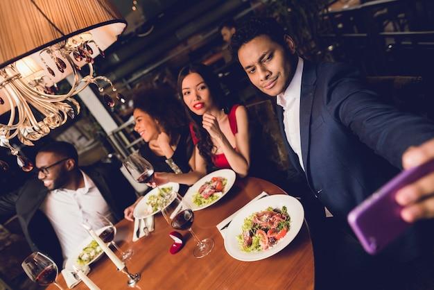男はレストランで友達とselfiesをします。