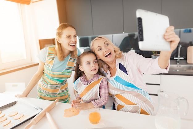 女性は台所で女の子とselfiesを作ります。