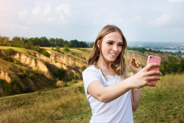 キャニオンでselfiesを作る自然を楽しんでいる若いブロンドの女性。ブログ