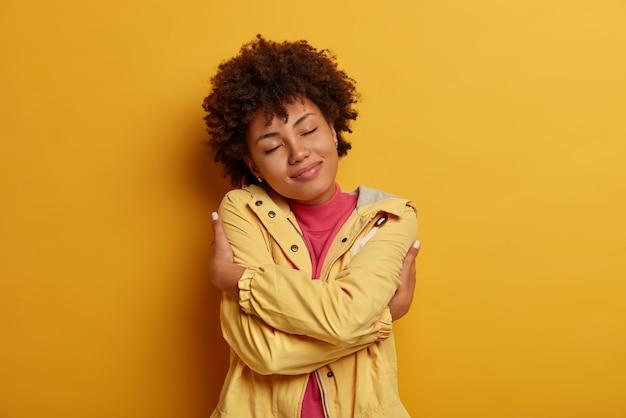 利己主義と自己愛の概念。喜んで暗い肌の巻き毛の女性モデルの肖像画は、自分自身を抱きしめ、体に手を交差させ、目を閉じたままにし、ジャケットを着て、黄色い壁にポーズをとる