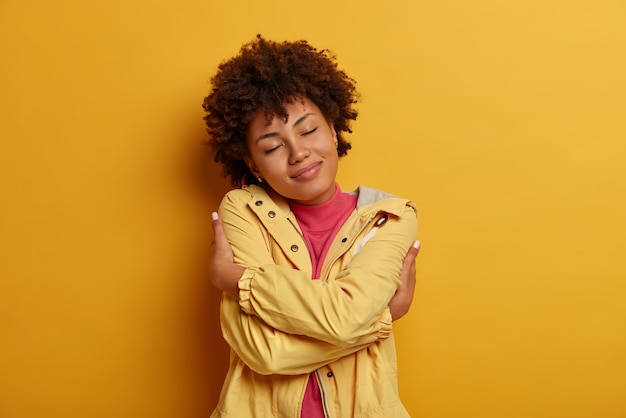 Selfishness and self love concept. portrait of pleased dark skinned curly female model hugs herself, crosses hands over body, keeps eyes closed, wears jacket, poses against yellow wall
