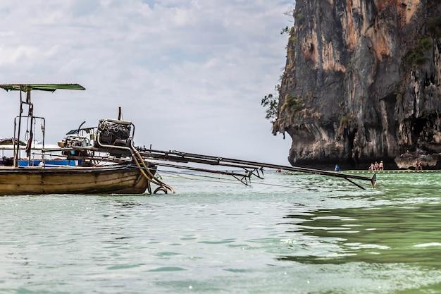 ピックアップトラックからの自作エンジンは、観光客と一緒にロングテールモーターボートの砂浜に取り付けられています
