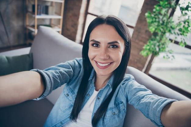 彼女の見栄えの良い魅力的な素敵なかなり陽気な陽気な女の子の自画像は、安全でモダンなロフトレンガの工業用住宅のアパートで家にいる自由な時間を検疫休暇を過ごすことを楽しんでいます