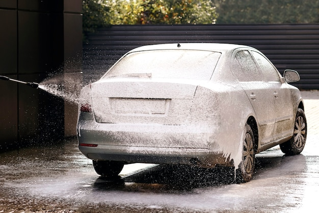 Selfservice car wash applying detergent on the car