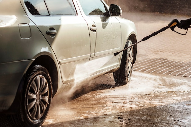 Selfservice car wash cleaning car using high pressure water