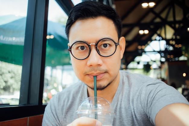 メガネselfyを持つ男自身がカフェでコーヒーを飲みます。