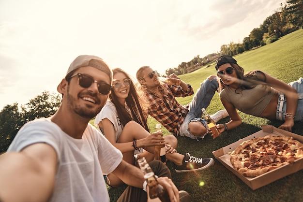 セライフタイム!屋外でピザやビールを楽しみながら笑顔のカジュアルウェアの若者の自画像