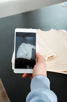 Sell online on the internet ecommerce store woman taking photo of clothes on smartphone selling