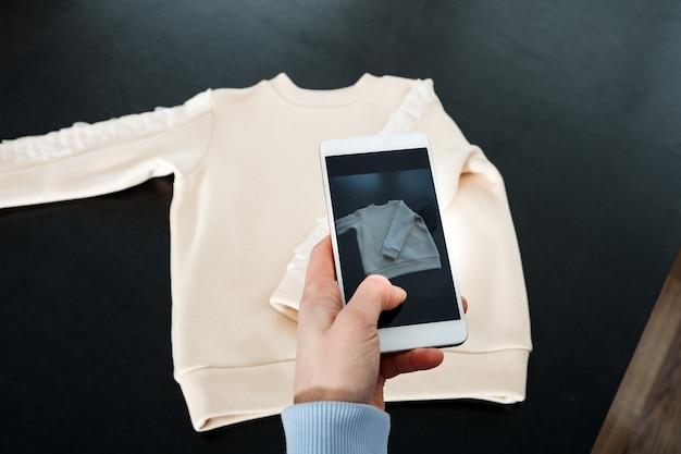 인터넷 전자 상거래 상점에서 온라인으로 판매 스마트 폰 판매에서 옷 사진을 찍는 여성
