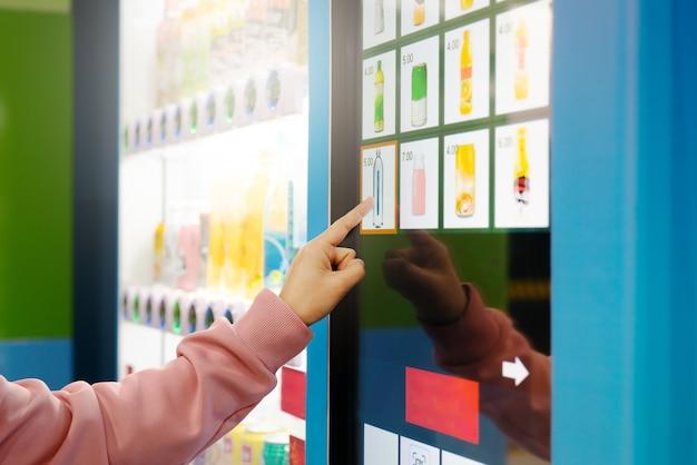 Продажа, технология и концепция потребления, женщина, покупающая с помощью торгового автомата