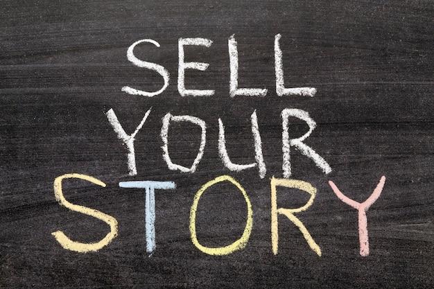 Sell your story phrase handwritten on the school blackboard