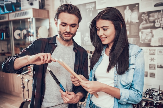 Seller demonstrates drumsticks to pretty girl in music store