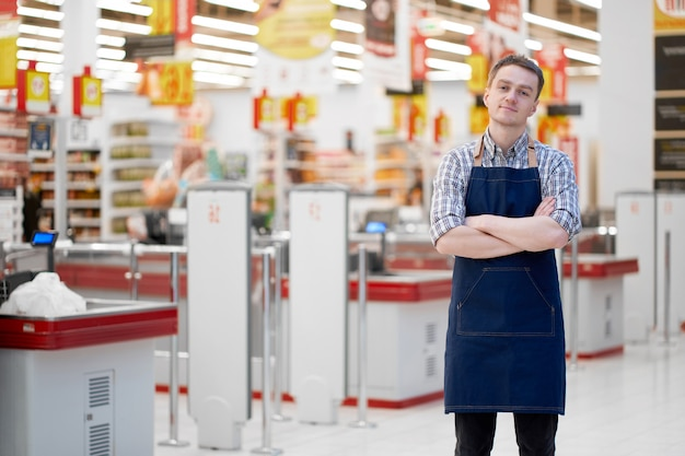 Seller in food store stands with crossed hands, copy space