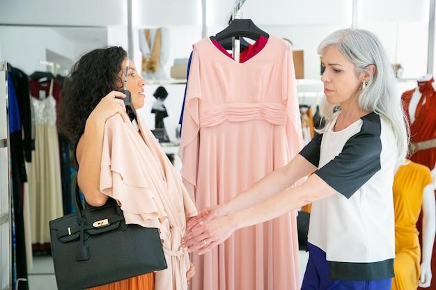 Продавец помогает покупателю выбрать ткань. женщина держит и показывает платье с вешалкой своему другу. вид сбоку. потребительство или концепция покупок