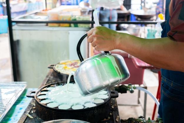 Продавец держит горшок тайских конфет на горячей сковороде
