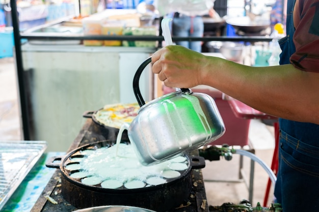 Seller holding a pot of thai sweetmeat on the hot pan