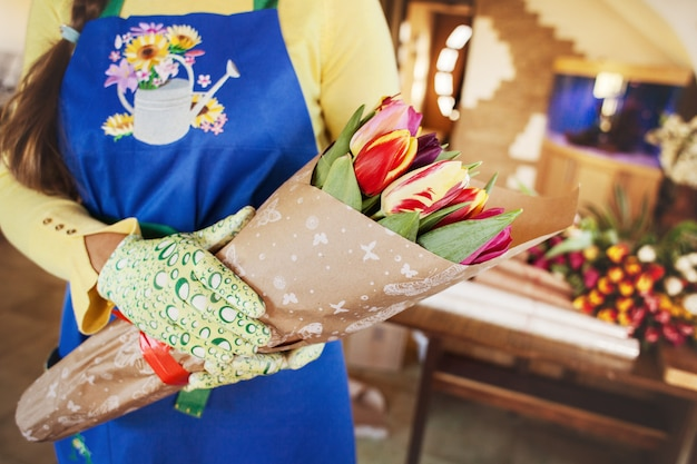 The seller holds a large beautiful bouquet of tulips packed in craft paper, side view