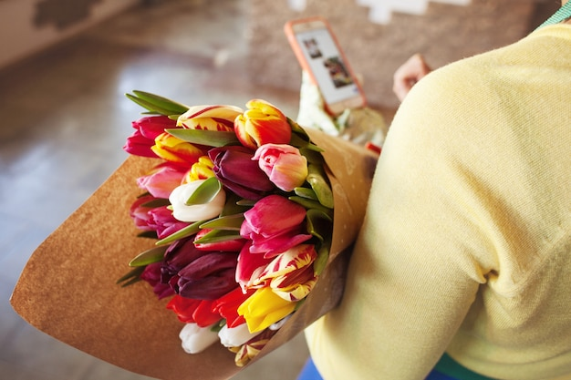 The seller holds a large beautiful bouquet of tulips packed in craft paper. top view