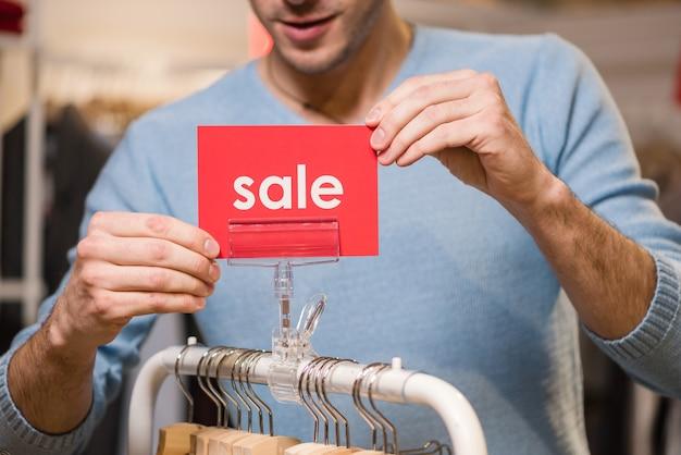 Продавец держит красные вывески со словом продажи