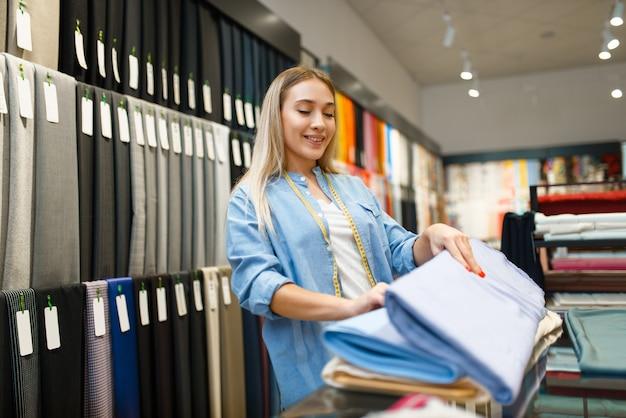 Продавец держит стопку ткани в текстильном магазине. полка с тканью для шитья