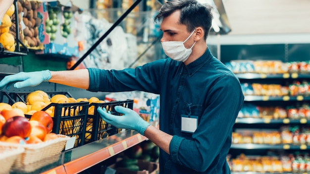 Продавец в защитной маске стоит перед прилавком с фруктами. коронавирус в городе