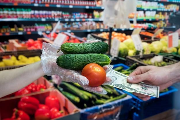 장갑을 낀 판매자는 신선한 야채를 판매합니다. 남자는 슈퍼마켓에서 식료품을 위해 달러를 준다. 코로나 19