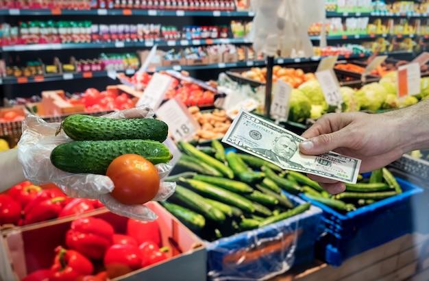 手袋の売り手は新鮮な野菜を販売しています