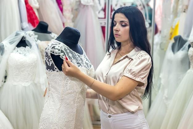 Продавец в свадебном салоне поправляет платье на манекене