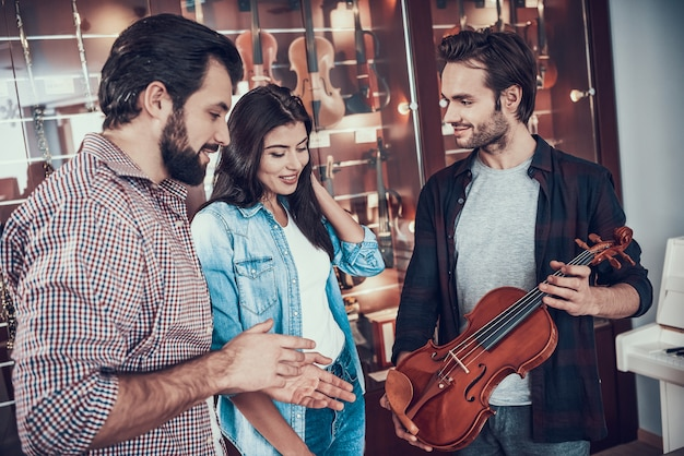Seller of musical instruments shows violin to couple.