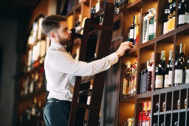 알코올 음료 판매자는 사다리에 서있는 병을 분류합니다.