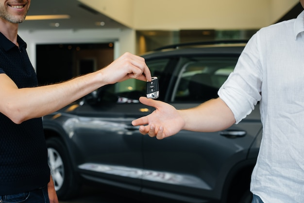 The seller passes the keys to a new car to a young family