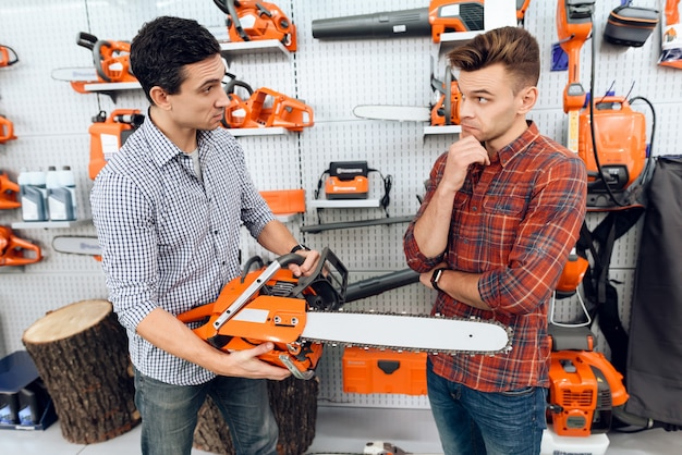 The seller in the store shows the customers a chainsaw.