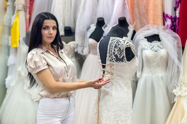 Seller in wedding salon correcting dress on mannequin