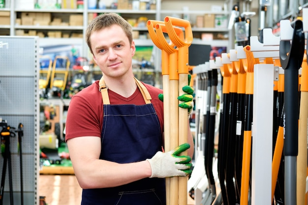 Продавец с инструментами оборудования в магазине