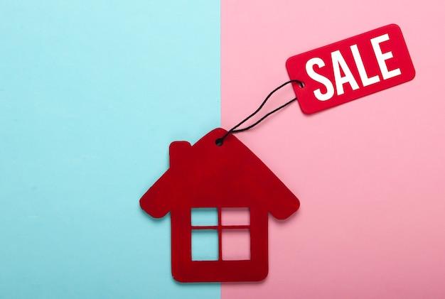 집을 파는 것. 핑크 블루 파스텔 배경에 판매 태그와 함께 빨간 집 입상. 평면도