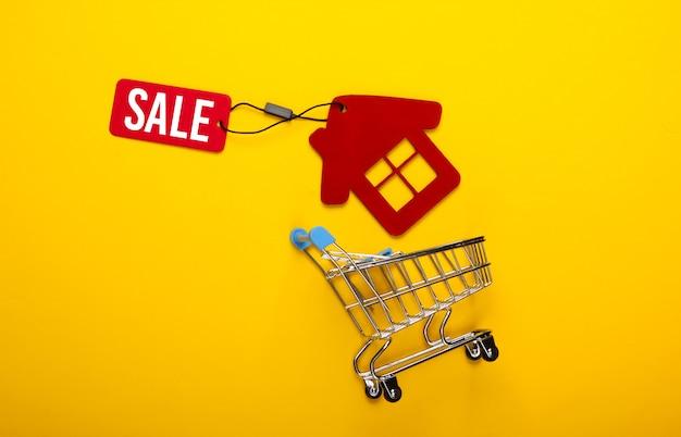 집을 파는 것. 노란색 배경에 판매 태그 쇼핑 트롤리와 빨간 집 입상. 평면도