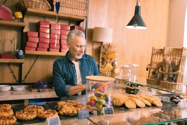 クッキーの販売。朝にクッキーを売っている間、喜びを感じているパン屋のひげを生やした白髪の所有者