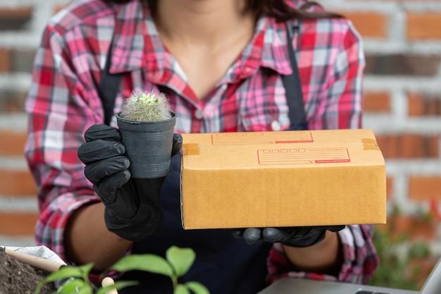植物をオンラインで販売する。植物のポットと配送ボックスを持っている手の写真を閉じる