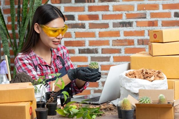 植物をオンラインで販売する。植物のポットを保持し、ラップトップで顧客と接続する女性